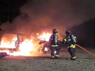 Firefighters extinguishing a vehicle fire